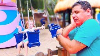 Настя и сонный папа гуляют в развлекательном парке